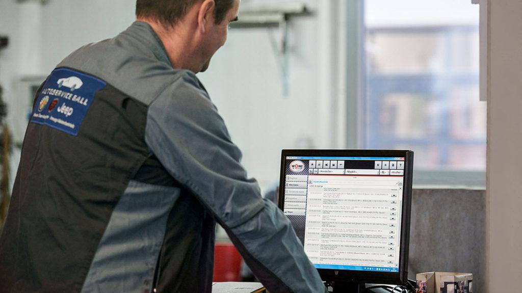 Autoservice Mann vor Monitor Muenchen