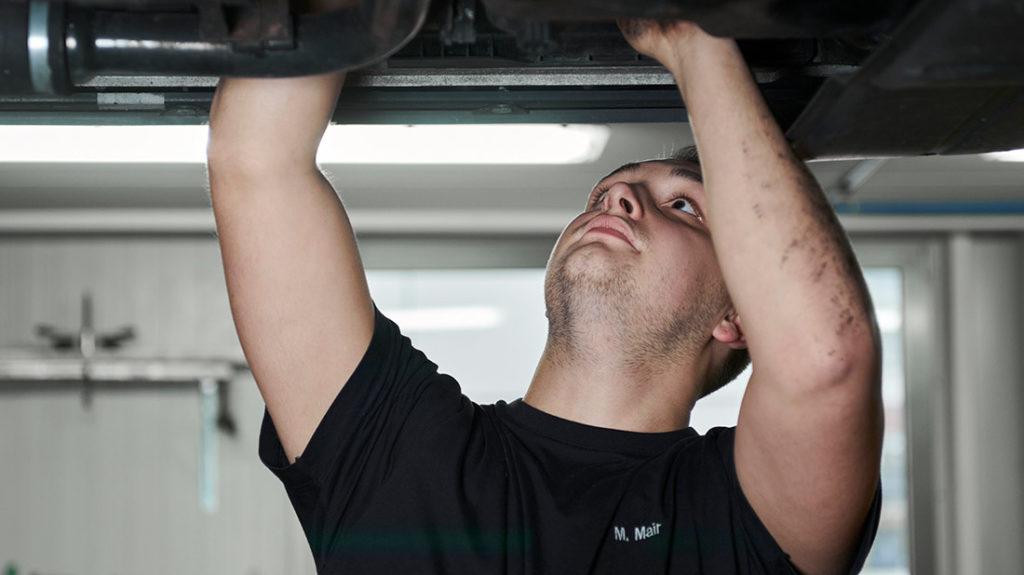 Autoservice Mitarbeiter repariert Auto Muenchen