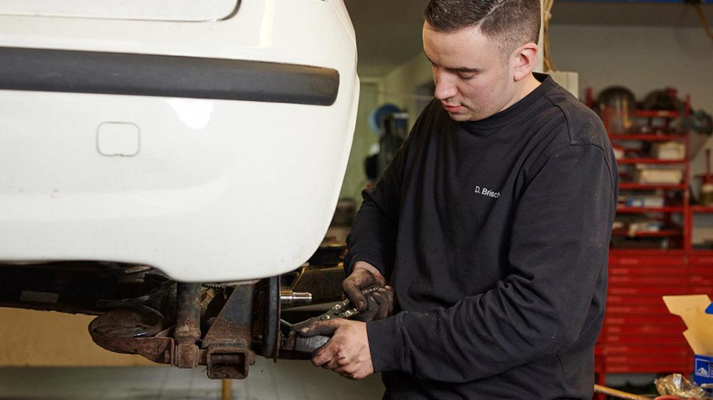 Autoservice Mitarbeiter schraubt an Reifen Muenchen