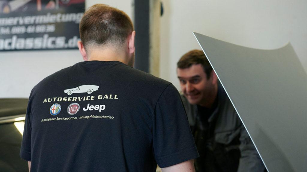 Autoservice zwei Mitarbeiter reparieren Auto Muenchen