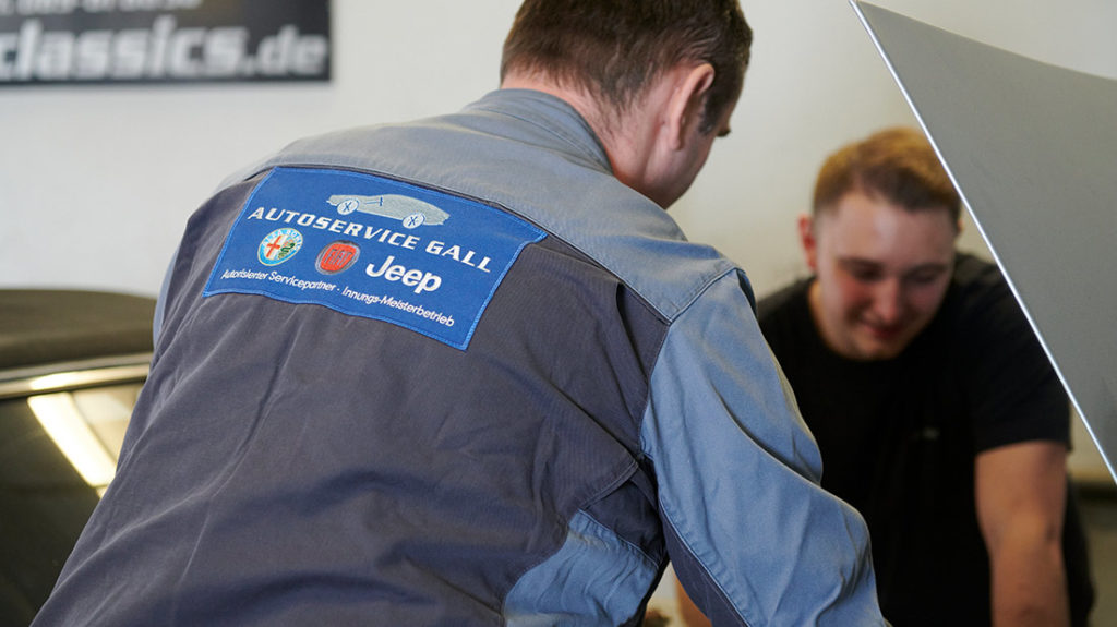 Autoservice zwei Mitarbeiter vor Motor Muenchen